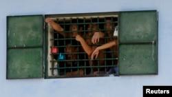 Para tahanan mengamati rekan-rekannya yang dibebaskan dari balik terali besi di penjara Hoang Tien, sekitar 100 kilometer dari kota Hanoi (Foto: dok). Human Right Watch melaporkan puluhan kasus kebrutalan polisi Vietnam yang banyak terjadi di penjara-penjara di seluruh negara tersebut, Selasa (16/9).