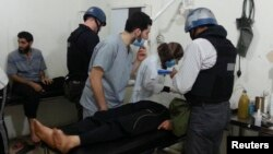 U.N. chemical weapons experts visit people affected by an apparent gas attack, at a hospital in the southwestern Damascus suburb of Mouadamiya, August 26, 2013.