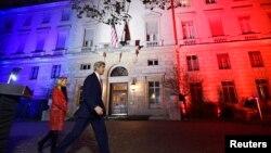 美国国务卿克里11月16日在巴黎美国大使馆讲话后和驻法大使哈特利步出使馆,背景建筑物上显示着空白蓝三色灯光,象征法国国旗。