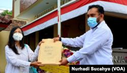 Ketua AJI Yogyakarta, Shinta Maharani menyerahkan karangan bunga dan dokumen berita Udin ke Polda DIY. (Foto: VOA/Nurhadi)