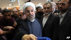 Presiden baru Iran Hassan Rowhani, mantan negosiator nuklir Iran, saat memberikan suara dalam pemilihan presiden (14/6). (AP/Vahid Salemi)
