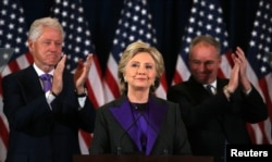 Hillary Clinton addresses her staff and supporters about the results of the U.S. election as former U.S. President Bill Clinton (L) and her running mate Tim Kaine applaud at a hotel in the Manhattan borough of New York, Nov. 9, 2016.