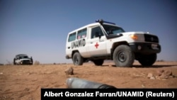 FILE - A UNAMID vehicle is parked near an unexploded ordnance during an operation to mark the location to warn the local population in North Darfur, March 27, 2011.
