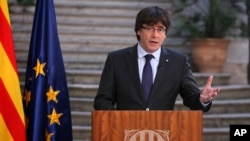 FILE - Carles Puigdemont delivers a statement at the Palau Generalitat in Barcelona, Spain, Oct. 28, 2017.