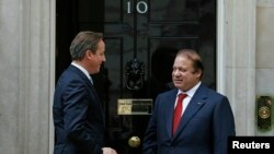 Britain's Prime Minister David Cameron (L) greets his Pakistani counterpart Nawaz Sharif as he arrives for their trilateral meeting with Afghan President Hamid Karzai, at Number 10 Downing Street in London, Oct. 29, 2013.