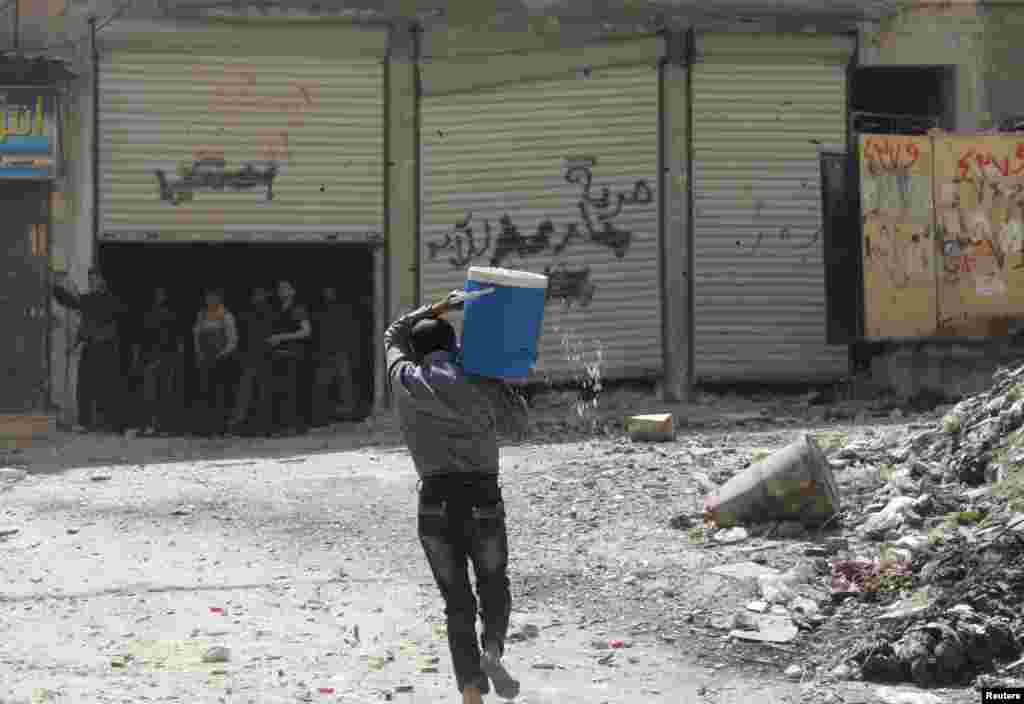 A man holding a water cooler runs to avoid a sniper in Aleppo's Salaheddine neighborhood, April 28, 2013.