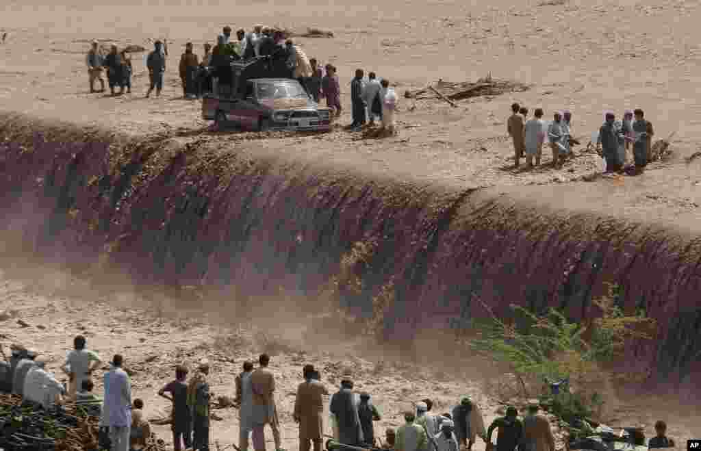 Pakistani villagers wade across a flooded road after heavy rain on the outskirts of Peshawar. Flash floods triggered by torrential rains killed dozens of people in northwest Pakistan, officials said.