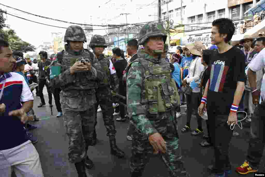 Thai military medics walk near the site of an explosion where 28 people were injured, Bangkok, Thailand, Jan. 19, 2014.