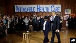 President Barack Obama walks in with volunteer Edna Pemberton before speaking with other volunteers who helped people enroll through the HealthCare.gov site at Temple Emanu-El, Nov. 6, 2013
