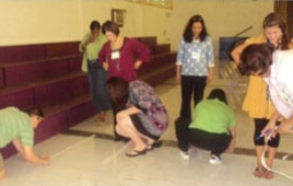 Teachers measure the distance of five steps during a Singapore Math training session.