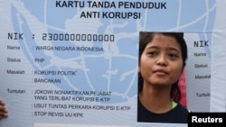 Seorang aktivis anti-korupsi memegang poster berbentuk KTP dalam unjuk rasa menuntut penyelidikan dugaan korupsi pengadaan e-ktp oleh para pejabat, di Jakarta, 19 Maret 2017. (Foto: Reuters)