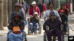 Phụ nữ lớn tuổi ngồi xe lăn được các nhân viên chăm sóc đẩy đến công viên ở Bắc Kinh.