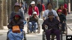 Sejumlah perempuan manula tengah menikmati suasana di sebuah taman di Beijing, Tiongkok dari atas kursi rodanya yang didorong oleh pekerja rumah jompo (Foto: dok). Pemerintah Tiongkok mengadakan amandemen terhadap UU Negara terkait pemeliharaan orang tua, yang mewajibkan anak-anak untuk menjenguk orang tua mereka lebih sering atau menghadapi gugatan pengadilan.