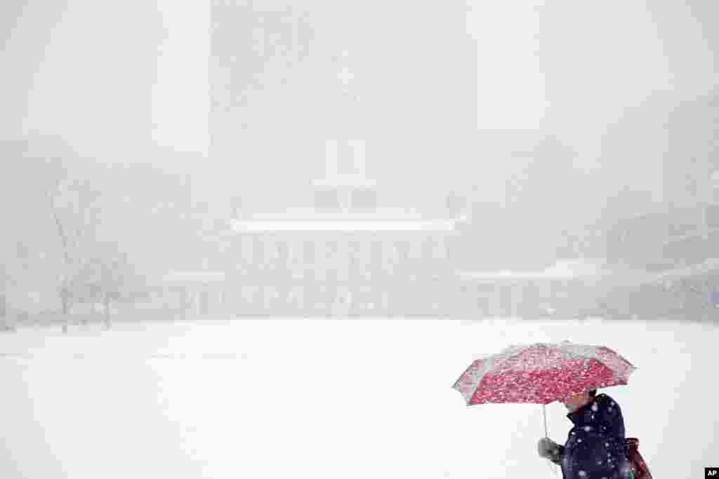 A woman walks past Independence Hall during a winter snowstorm in Philadelphia, Pennsylvania, Dec. 10, 2013.