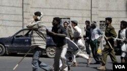 Kelompok pendukung pemerintah mengejar demonstran anti-pemerintah dalam bentrokan di Sana'a.