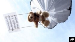 Teddy bear hangs on parachute during protest training for Belarusian airspace intrusion by Swedish human rights activist, Stockholm, July 2012.