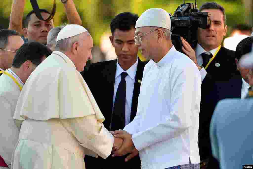 Paus Fransiskus berjabat tangan dengan Presiden Myanmar Htin Kyaw saat dia tiba di Istana Kepresidenan di Naypyitaw, 28 November 2017.
