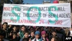 """Антиправительственнная демонстрация на севере Сирии. На плакате написано: """"Мир. Твое позорное бездействие приведет к появлению тысяч Бин Ладенов"""""""