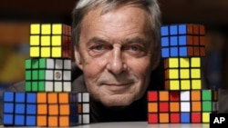 FILE - Erno Rubik, the inventor of the Rubik's Cube, poses with cubes at Liberty Science Center, Wednesday, April 25, 2012, in Jersey City, N.J. An extremely small Rubik's Cube has gone on sale in Japan for 198,000 yen, or about $1,900. (AP Photo/Julio Cortez)