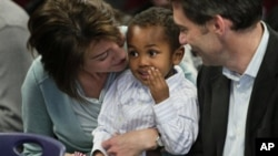 Theodore Lieberman, 2, adopted from Ethiopia, sits between his parents Jamie, right, and Aaron Lieberman, during the U.S. Citizenship and Immigration Services (USCIS) first ever Adoption Day ceremony,18 Nov 2010