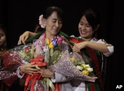 FILE - Burmese democracy leader Aung San Suu Kyi receives a traditional Chin shawl before speaking in Fort Wayne, Indiana, Sept. 25, 2012.