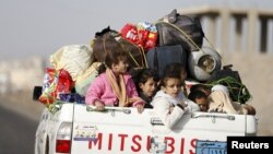 FILE - Children ride on the back of a pick-up truck with their luggage as they flee Saudi-led air strikes in Sanaa, April 6, 2015.