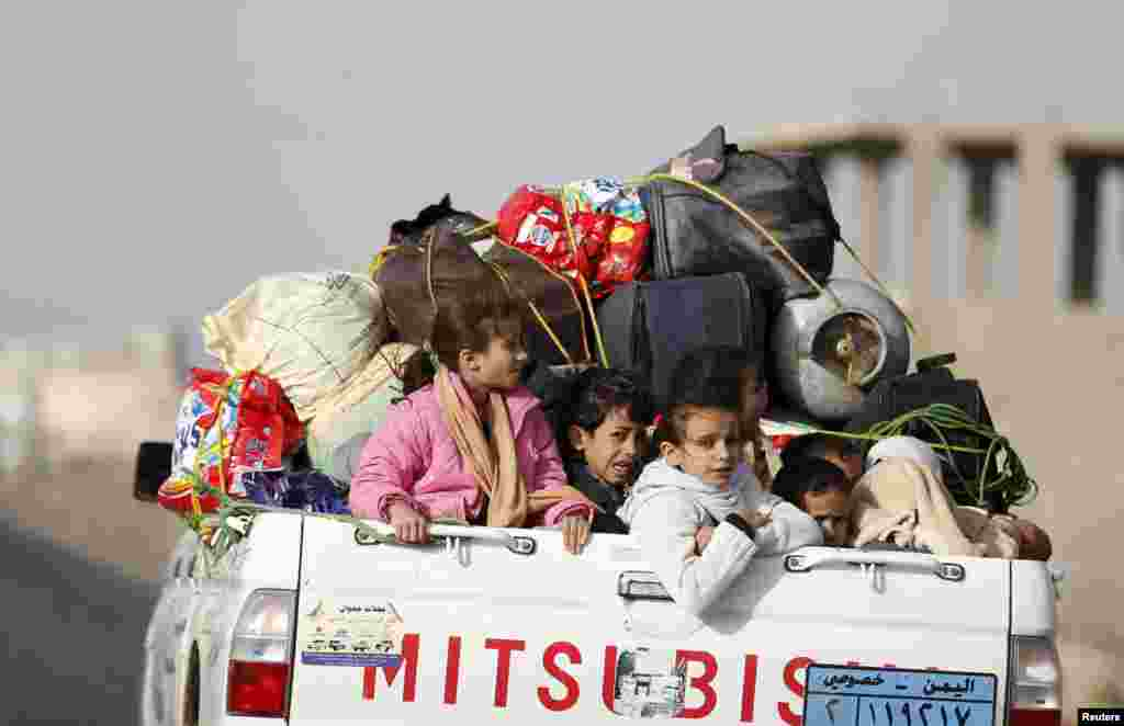 Children ride on the back of a pick-up truck with their luggage as they flee Saudi-led airstrikes in Sana'a, April 6, 2015.