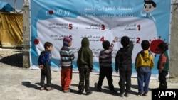 شام میں بچے کرونا وائرس سے آگاہی کے لیے لگائے گئے بینر کو دیکھ رہے ہیں