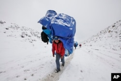 FILE - A porter walks with a massive load towards Everest Base camp near Lobuche, Nepal, March 28, 2016. After two hard years for mountaineers, more than 200 climbers have scaled the daunting mountain in the past 10 days, sending a wave of optimism throug
