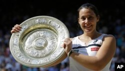 Marion Bartoli dari Perancis dengan trofi Wimbledon (6/7). (AP/Anja Niedringhaus)