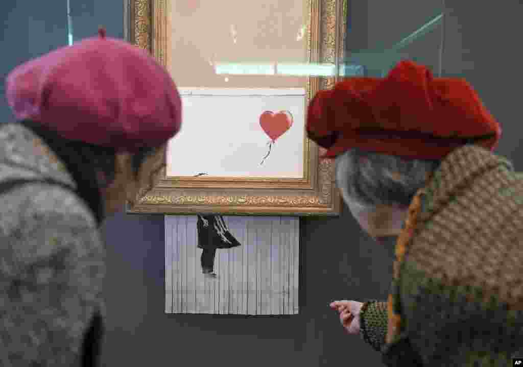 "People look at the shredded Banksy painting ""Love is in the Bin' at the Museum Frieder Burda in Baden-Baden where the work will be shown from Feb. 5 to March 3, 2019."