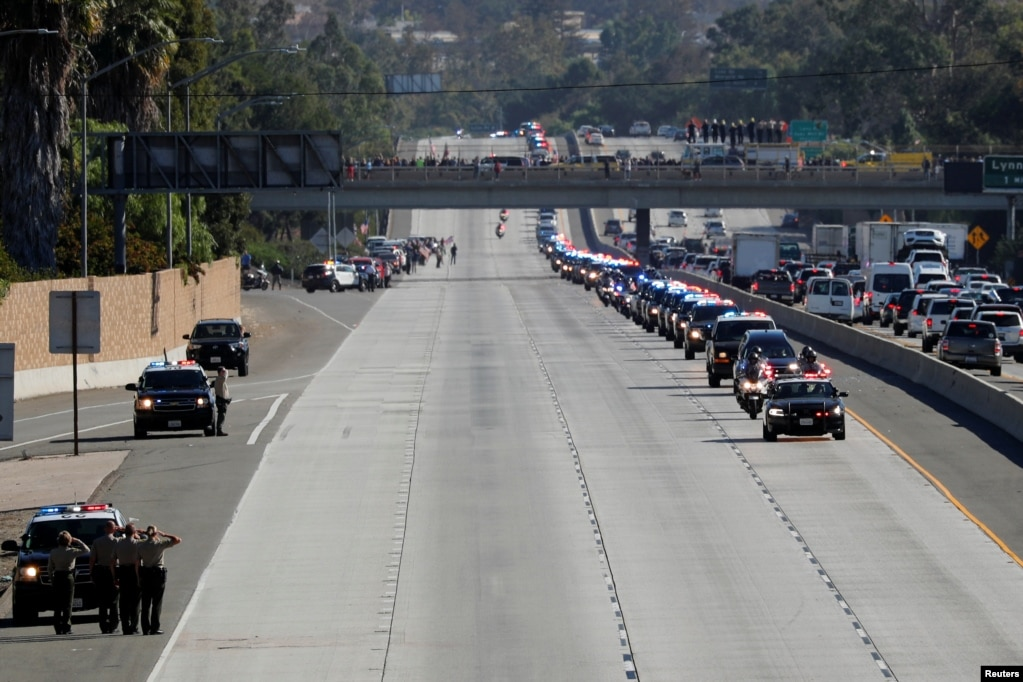 A procession for the body of Sheriff Sgt. Ron Helus, who was killed in a mass shooting at a Southern California bar, drives along Ventura Highway 101 in Thousand Oaks, California. Twelve people were killed by a gunman late Wednesday. Helus was immediately hit with numerous gunshots after going inside to confront the shooter, and he died after being taken to a hospital.