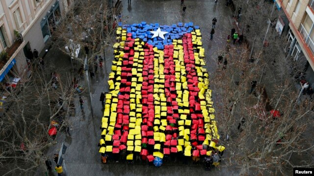 People hold placards to form a giant Catalan flag in front of Sant Feliu townhall, near Barcelona, Feb. 16, 2014.