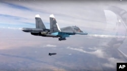 ພາບນີ້ໄດ້ມາຈາກວີດີໂອຈາກເວັບໄຊທ໌ທາງການຂອງກະຊວງປ້ອງກັນປະເທດ ຣັດເຊຍ ໃນວັນທີ 9 ຕຸລາ, 2015, ລະເບີດຖືກຍິງອອກຈາກເຮືອບິນຮົບ Su-34 ຂອງ ຣັດເຊຍ ໃສ່ພວກນັກຮົບໃນ ຊີເຣຍ.