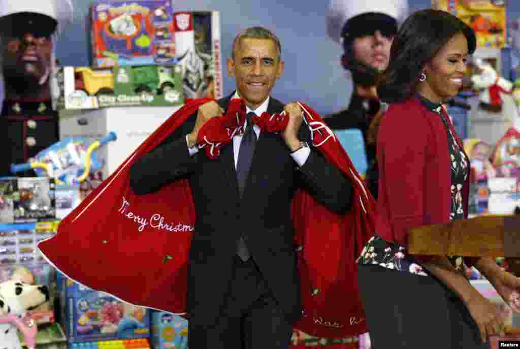 U.S. First Lady Michelle Obama smiles as President Barack Obama arrives with sacks of toys and gifts from the Executive Office of the President staff to donate to the Marine Corps Toys for Tots Campaign in Washington, Dec. 10, 2014.