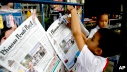 A Cambodian boy hangs up copies of the English-language newspaper, Phnom Penh Post, at the newsstand in Phnom Penh, file photo.