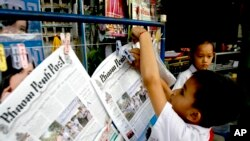 FILE PHOTO - A Cambodian boy hangs up copies of the English-language newspaper, Phnom Penh Post, at the newsstand in Phnom Penh, Cambodia.