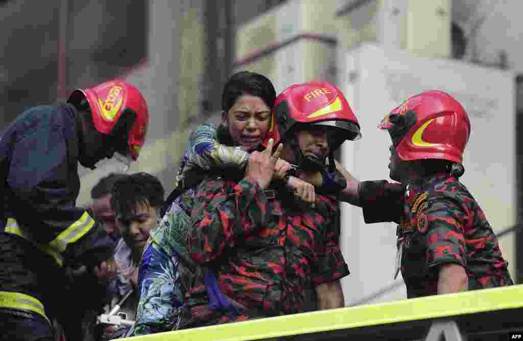 A Bangladeshi survivor reacts after being rescued by firefighters from a burning office building in Dhaka.
