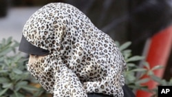 A Muslim woman passes a cafe with her face covered in Milan (file photo)