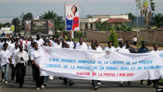 Burundian journalists carry a banner as they march in the streets of Burundi's capital Bujumbura, May 3, 2011.