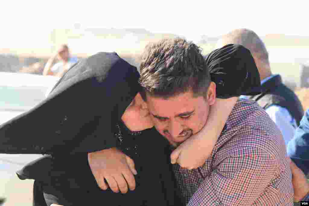 A mother weeps and hugs her son, who she hadn't seen in the two and a half years while he was trapped at the Khazir camp in Kurdish Iraq. (H. Murdock/VOA)