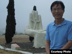 Tác giả đứng bên tượng đài Hand of Hope, Bàn tay Hy vọng, tác phẩm của nhà điêu khắc Nguyễn Lưu Đạt (ảnh Bùi Văn Phú)