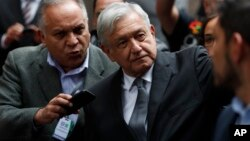 Mexico's President Andres Manuel Lopez Obrador waves as he arrives for the swearing-in ceremony for Mayor-elect Claudia Sheinbaum, in Mexico City, Dec. 5, 2018.