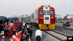 FILE - Kenyan President Uhuru Kenyatta, third from left, watches the opening of the SGR cargo train as it leaves the port containers depot in Mombasa to Nairobi, May 30, 2017. The project, a $3.3 billion investment backed by China, is the country's largest infrastructure project.