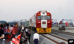 FILE - Kenyan President Uhuru Kenyatta (3rd-L) watches the opening of the SGR cargo train as it leaves the port containers depot in Mombasa to Nairobi, May 30, 2017. The project, a $3.3 billion investment backed by China, is the country's largest infrastructure undertaking since independence.