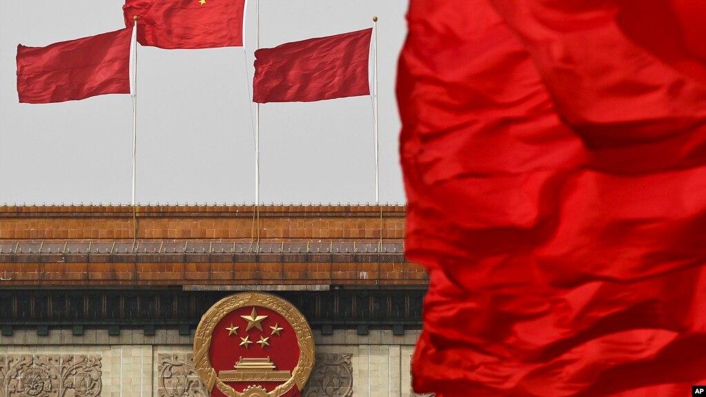 中国国旗在北京人大会堂悬挂的国徽上空飘扬。(资料照片)