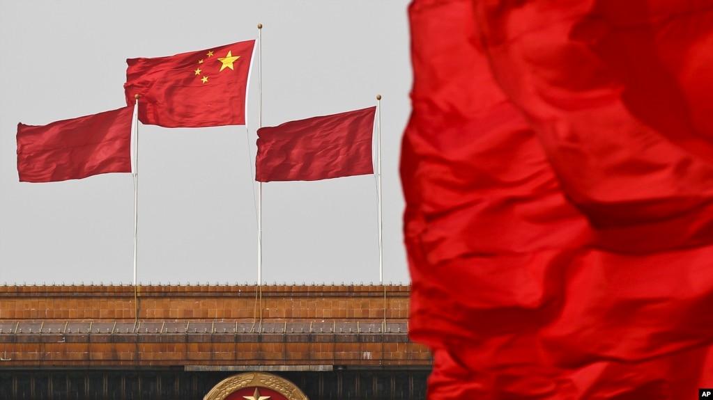 中國國旗在北京人大會堂懸掛的國徽上空飄揚。 (資料照片)