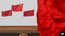 中國國旗在北京人大會堂懸挂的國徽上空飄揚。(資料圖片)