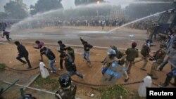 Polisi India menggunakan meriam air dan gas air mata untuk membubarkan para pengunjuk rasa di New Delhi (23/12). Seorang polisi yang terluka parah pasca bentrokan dengan para demonstran ini dikabarkan meninggal dunia di rumah sakit, hari ini.