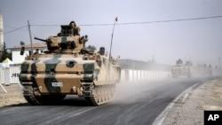 Tank-tank dan kendaraan lapis baja tentara Turki bergerak menuju perbatasan Suriah, Karkamis, di Turki (25/8). (AP/Halit Onur Sandal)